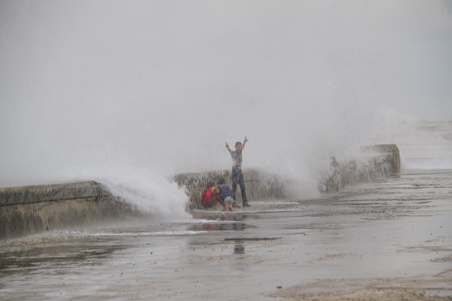 Kids playing on Malecon getting showered by the sea