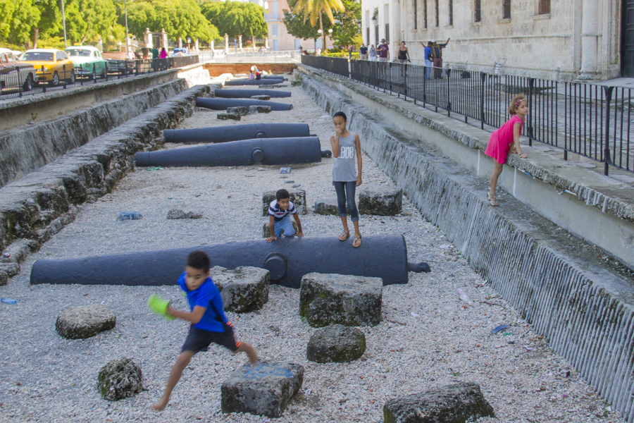 Kids playing on top of old cannons in Old Havana