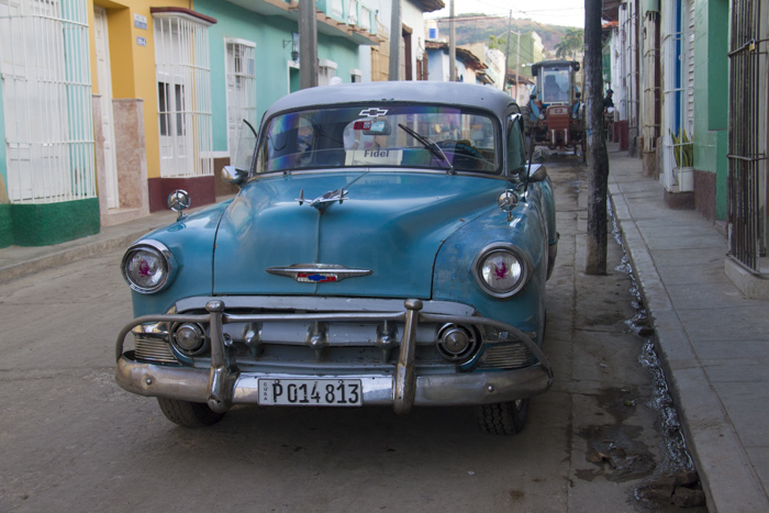 Blue classic car with Fidel sign in the street of Trinidad, Cuba