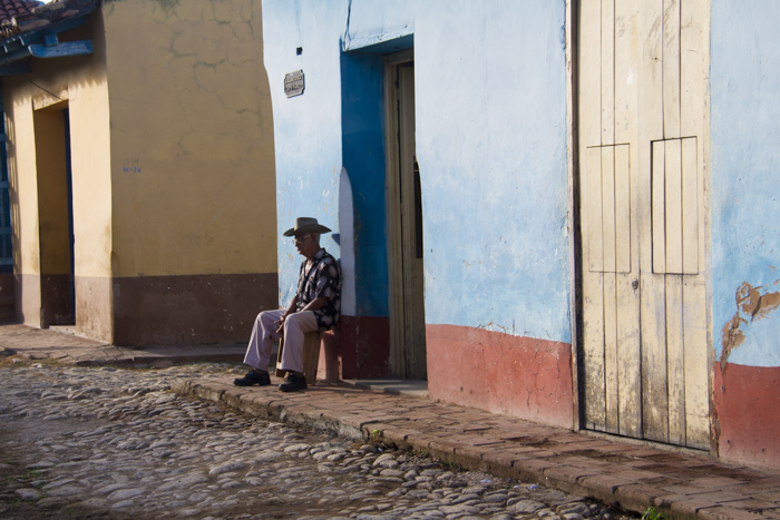 Man sitting in the colourful street of Trinidad, Cuba