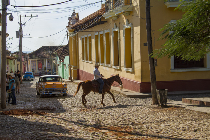 Man riding a horse, in a colourful street in Trinidad, Cuba