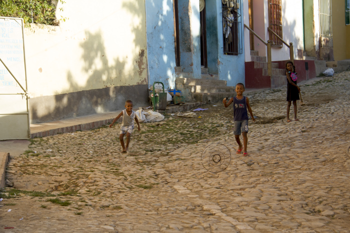 Kids playing with a broken fan in the streets of Trinidad, Cuba